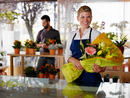 tezgâhtar: Female sales assistant working as florist and holding bouquet with customer in background. Horizontal shape, waist up