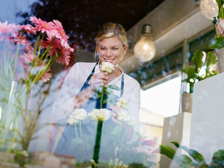 Young attractive woman working in flower shop, preparing bouquet and smelling white roses photo