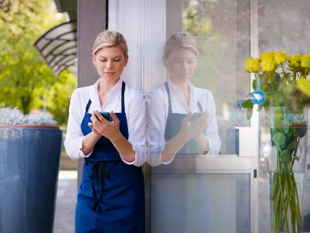 Portrait of beautiful caucasian girl self-employed in flower shop, smiling and using mobile phone. Horizontal shape, waist up photo