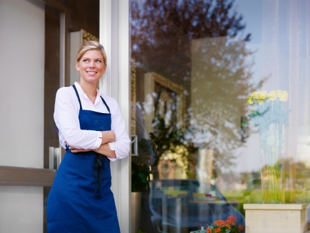 business owner: Portrait of beautiful caucasian girl self-employed in flower shop, smiling and looking away. Horizontal shape, waist up, copy space