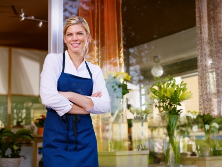Portrait of beautiful caucasian girl self-employed in flower shop, smiling and looking at camera. Horizontal shape, waist up photo