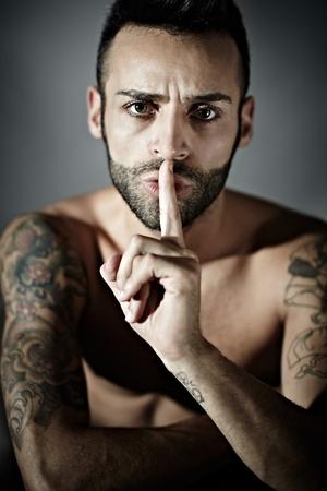 hissing: ritratto di uomo fiero giovane adulto con sibili tatuaggi. Forma verticale, vista frontale, studio shot Archivio Fotografico