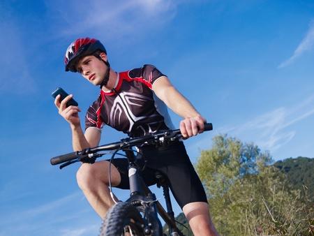 the rider: attivit� sportiva: ciclista giovane adulto a cavallo in mountain bike e messaggi di testo sul cellulare. Forma orizzontale, Inquadratura dal basso, copia spazio