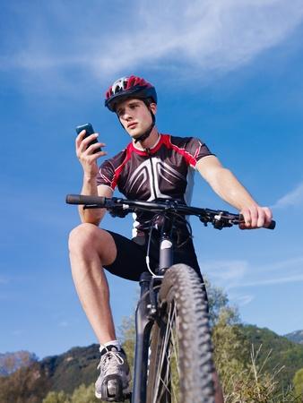 ropa deportiva: actividad de deportes: joven ciclista adulto montando bicicleta de monta�a y mensajes de m�vil de texto. Forma vertical, �ngulo baja visi�n Foto de archivo