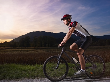 sports activity: young adult cyclist riding fast mountain bike in the countryside. Horizontal shape, side view, full length, copy space