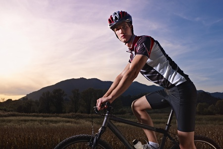 sports activity: young adult cyclist riding mountain bike in the countryside. Horizontal shape, side view, copy space photo