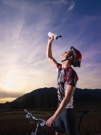 sports activity: young adult cyclist on mountain bike spilling water on face from bottle. Vertical shape, side view, copy space photo