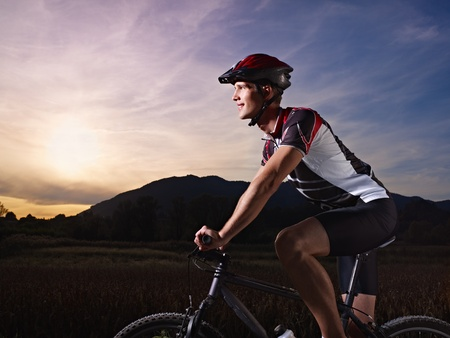 mountain bicycle: sports activity: young adult cyclist riding mountain bike in the countryside. Horizontal shape, side view, copy space
