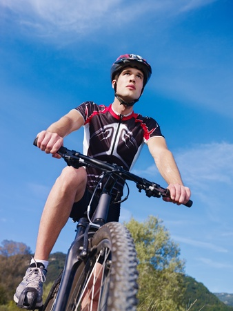 young adult cyclist riding mountain bike in the countryside photo