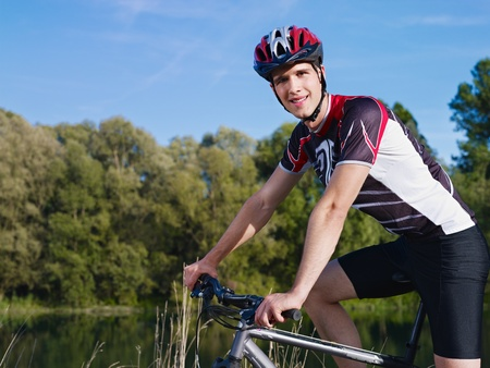 young adult cyclist riding mountain bike in the countryside and looking at camera photo