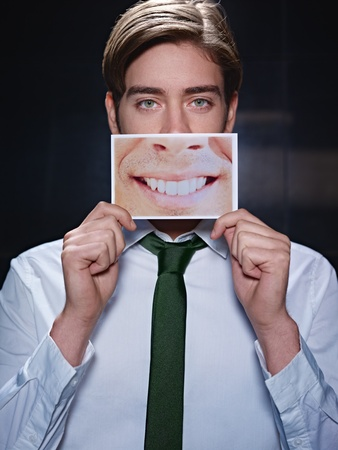 young business man holding photo of toothy smile on black background. Vertical shape, front view, waist up photo