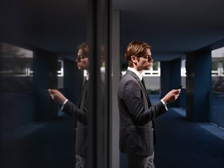 half dressed: young business man standing out of office building and reading emails on mobile phone. Horizontal shape, waist up, copy space Stock Photo