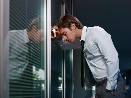 jong volwassen Italiaanse zakenman sloeg zijn hoofd tegen een raam in het kantoor. Horizontale vorm, kopie ruimte