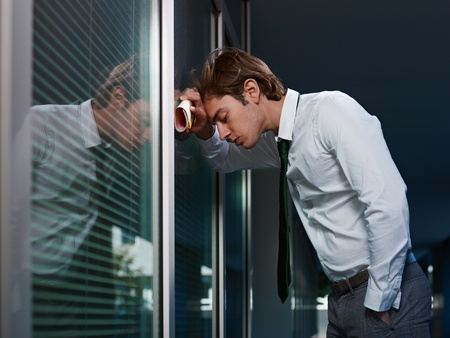 loser: young adult italian business man banging his head against a window in office. Horizontal shape, copy space Stock Photo