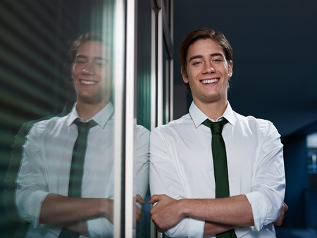 young business man leaning on office window with arms crossed and looking at camera smiling. Horizontal shape, front view, waist up Stock Photo - 10907009