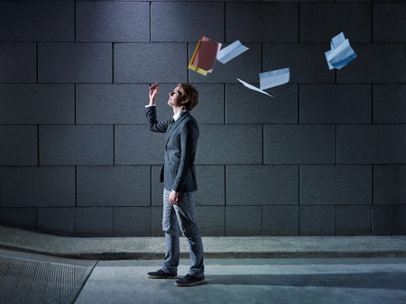 young business man walking out from office parking and throwing away paperworks. Horizontal shape, side view, copy space