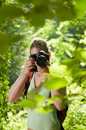 animal watching: young woman trekking among trees and taking pictures with dslr camera. Vertical shape, front view, waist up