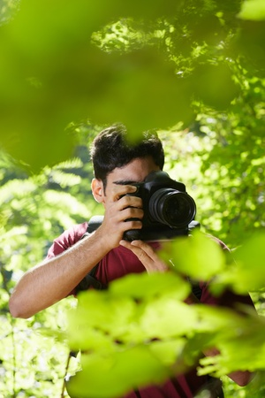 birdwatching: young hispanic man trekking among trees and taking pictures with dslr camera. Vertical shape, front view, copy space Stock Photo