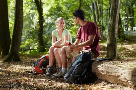 junger Mann und Frau beim Mittagessen mit Sandwich während Wanderausflug. Horizontale Form, in voller Länge