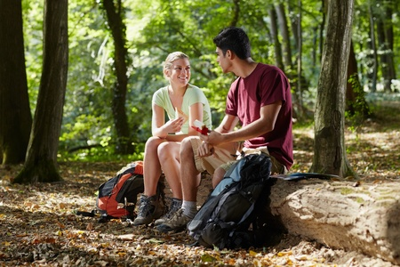 jungle girl: young man and woman having lunch with sandwich during hiking excursion. Horizontal shape, full length Stock Photo