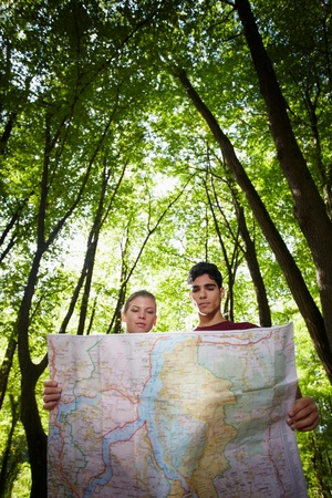 young man and woman checking map during hiking excursion and look for destination. Vertical shape, low angle view Stock Photo - 10996054