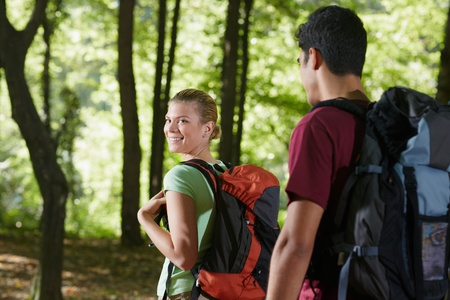 woman hiking: young man and woman during hiking excursion, with woman looking over shoulders. Horizontal shape, rear view, waist up