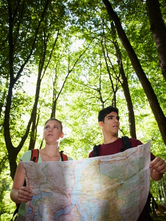 young man and woman got lost during hiking excursion and look for destination on map. Vertical shape, waist up photo