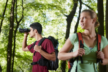 waist up: young people trekking among trees and looking at birds with binoculars. Horizontal shape, side view, waist up