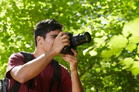young hispanic man trekking among trees and taking pictures with dslr camera. Horizontal shape, side view, copy space Stock Photo - 11160114