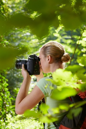 dslr: young woman trekking among trees and taking pictures with dslr camera. Vertical shape, side view, waist up, copy space Stock Photo