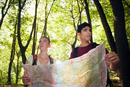 look for: young man and woman got lost during hiking excursion and look for destination on map. Horizontal shape, waist up Stock Photo
