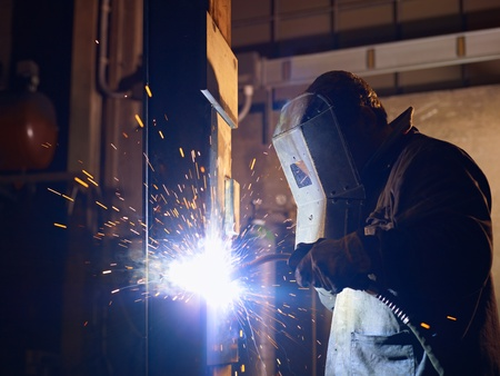 welding metal: Manual worker in steel factory using welding mask, tools and machinery on metal. Horizontal shape, side view, waist up Stock Photo