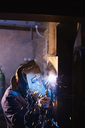 machinery space: Manual worker in steel factory using welding mask, tools and machinery on metal. Vertical shape, side view, copy space