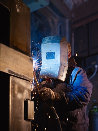 structural: Manual worker in steel factory using welding mask, tools and machinery on metal. Vertical shape, side view, waist up