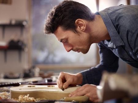 artisanale: medio volwassen man aan het werk als ambachtsman in het Italiaans workshop met gitaren en muziekinstrumenten, gitaar glad lichaam