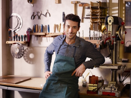 owner: Portrait of adult italian man at work as craftsman in shop with tools in background