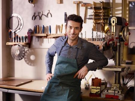 artisanale: Portret van de volwassen Italiaanse man op het werk als vakman in de winkel met hulpmiddelen op de achtergrond Stockfoto