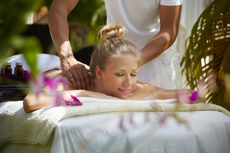 massage table: Young beautiful blonde caucasian woman gets massage and beauty treatment in luxury resort. Horizontal shape, side view