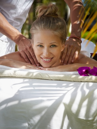 Young beautiful blonde caucasian woman gets massage and beauty treatment in luxury resort photo