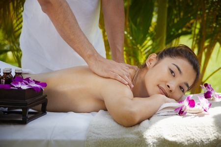 Young beautiful asian woman gets massage and beauty treatment in luxury resort. Side view photo