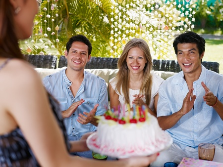 guests: Birthday party with cake, drinks and happy caucasian and asian friends clapping hands. Front view