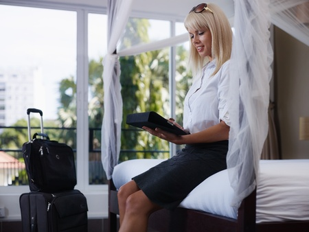 hotel bedroom: Mid adult caucasian businesswoman typing on tablet pc in hotel room during business travel. Side view, three quarter length