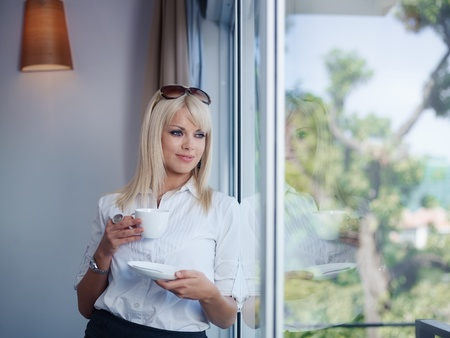 Mid adult businesswoman relaxing and drinking a cup of tea, looking out of window. Waist up, front view, copy space photo