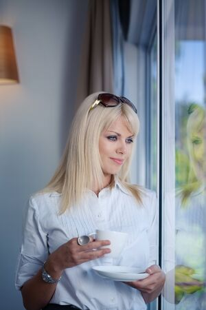 Mid adult businesswoman relaxing and drinking a cup of tea, looking out of window. Waist up, side view, copy space photo