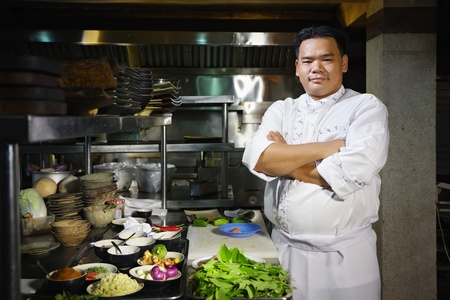 Portrait of adult man at work as chef in the kitchen of an Asian restaurant, posing with arms crossed photo