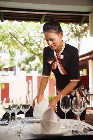 waist up: young woman working as waitress in exclusive restaurant, setting up a table. Waist up, side view