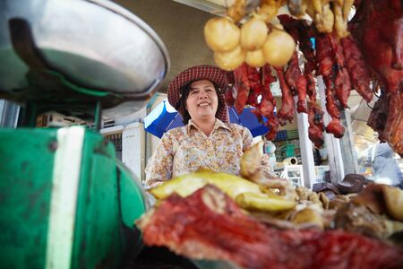 phnom: Asian woman selling meat, beef, pork and chicken at street restaurant in Phnom Penh, Cambodia Stock Photo