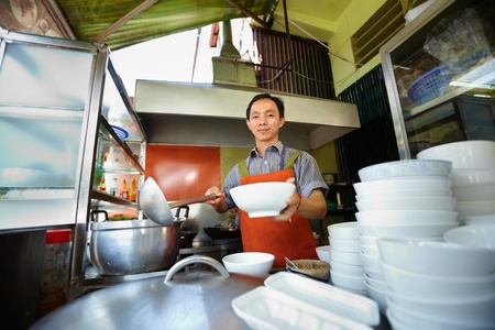 Chef preparing traditional Asian street food and working in the restaurant kitchen. Horizontal shape, front view Stock Photo - 11791631