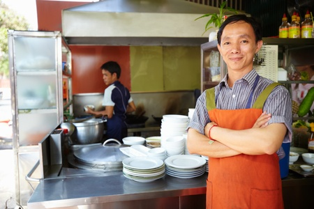 Portrait of chef at Asian street food restaurant, looking at camera with arms crossed. Horizontal shape, front view