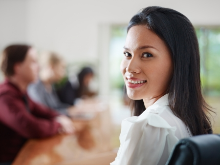 elegant business man: Attractive young Asian business woman smiling and looking over shoulders at business meeting with co-workers.